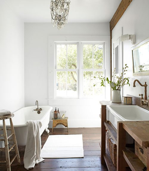 Bright bathroom with vintage claw-foot tub and chandelier. Photographed by Björn Wallander