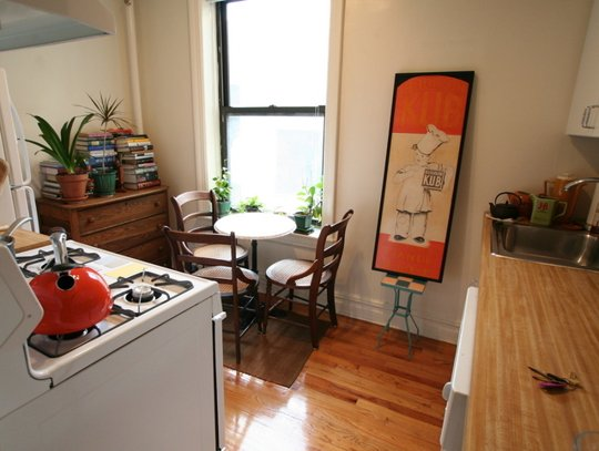 Love this intimate kitchen with small plants and pops of orange in the art and kettle. Via apartment therapy