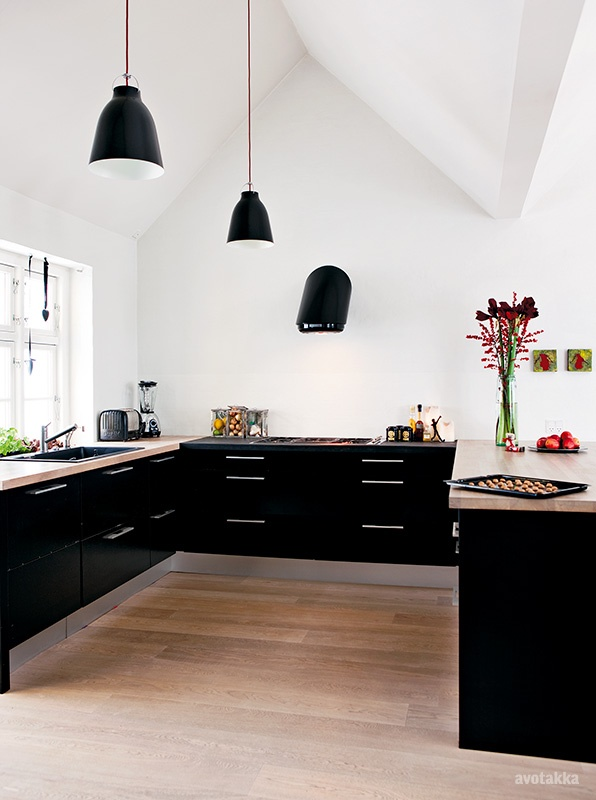 Spacious and light-filled black and white kitchen. Lovely fruit and flower details. Photo via avotakka