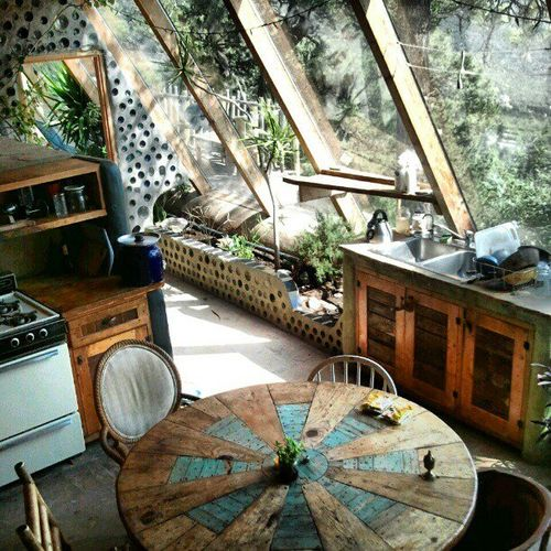 Slanted windows with views of nature and a lovely mandala table. Earthship kitchen via frommoontomoon via observando.net